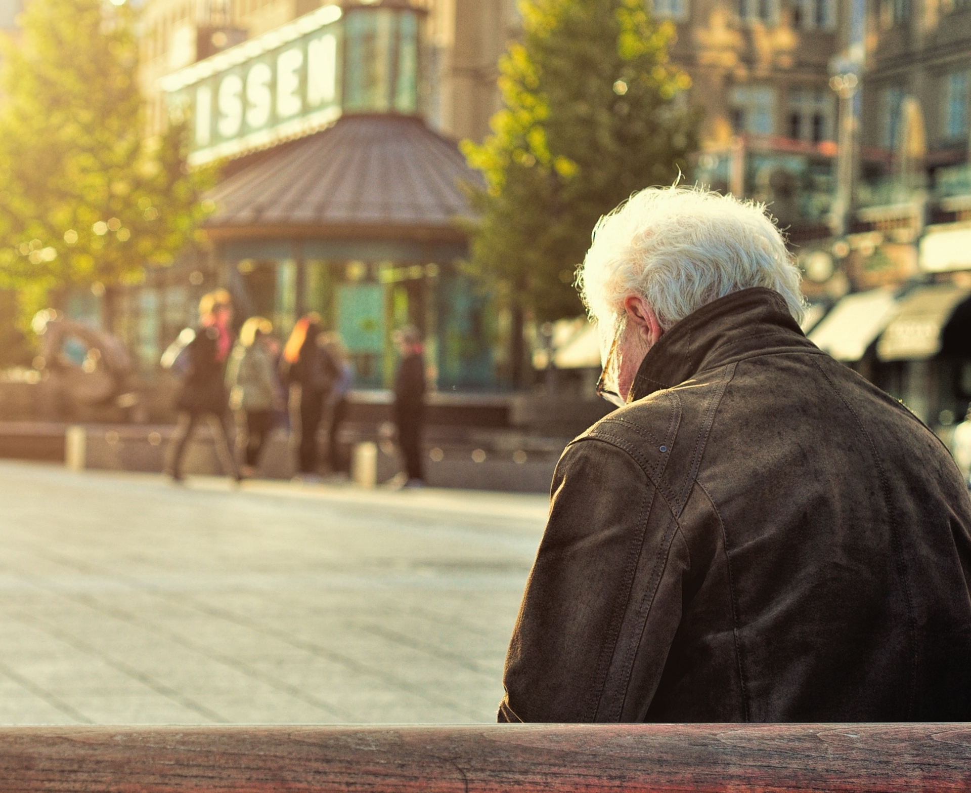 Lonely elder man sitting at a bench
