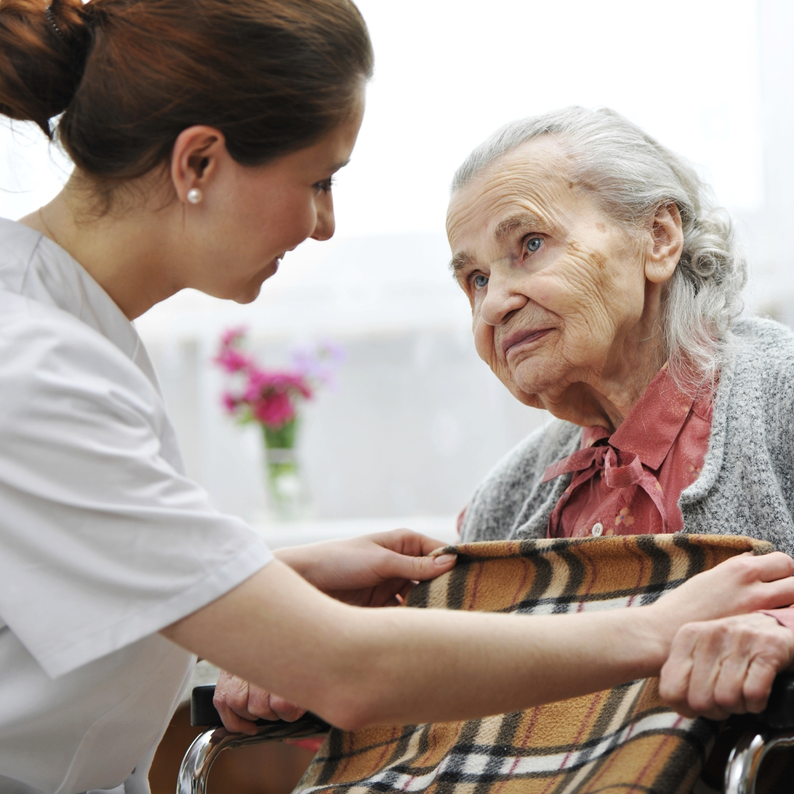 Smiling nurse taking care of old woman